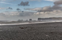 Пляж Reynisfjara отработанной формовочной смеси в Исландии Утесы в воде волны волны океана переднего плана фокуса ветрено стоковые изображения rf