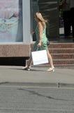 рабаты сбывание Leggy молодая женщина в зеленом платье и белых высоких пятках идя вниз с улицы за магазинами стоковые фото
