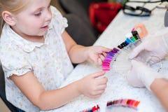 Работайте в мастере студии ногтя с ребенком клиента Стоковые Фото