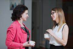 Работайте коллеги в офисе говоря друг к другу во время пролома Стоковое Изображение