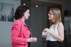 Работайте коллеги в офисе говоря друг к другу во время пролома Стоковое фото RF
