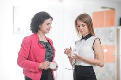Работайте коллеги в офисе говоря друг к другу во время пролома Стоковое Фото