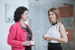 Работайте коллеги в офисе говоря друг к другу во время пролома Стоковое Изображение RF