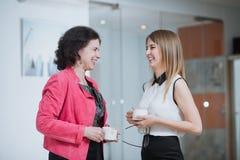 Работайте коллеги в офисе говоря друг к другу во время пролома Стоковые Изображения RF