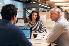 Работайте коллеги говоря стратегию совместно в офисе Стоковое фото RF