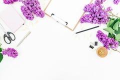 Работать места для работы блоггера с доской сзажимом для бумаги, тетрадью, ножницами, сиренью и аксессуарами на белой предпосылке стоковое изображение