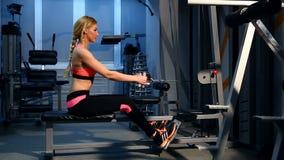 Работать перекрестной тренировки женщины разминки cardio используя машину rowing в спортзале фитнеса Азиатская девушка разрабатыв видеоматериал