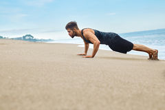 Работать человека фитнеса, делая нажимает поднимает тренировку на пляже спорты Стоковая Фотография RF