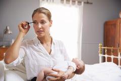 Работающая мать держа младенца и кладя дальше составляет стоковое фото