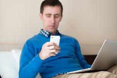 Работающий на самого себя бизнесмен используя телефон и компьтер-книжку стоковые изображения