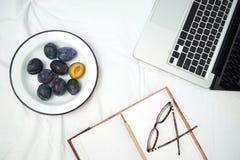 Работающ в кровати, компьтер-книжке и тетради на белой кровати Стоковое Изображение