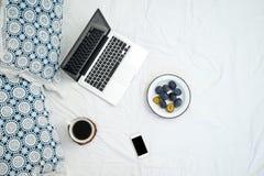 Работающ в кровати, компьтер-книжке и чашке кофе на белой кровати Стоковое Фото