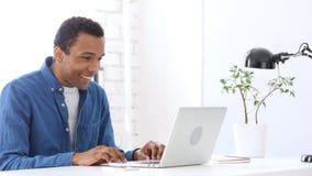 Работающ на компьтер-книжке в офисе, счастливый Афро-американский человек стоковые фото