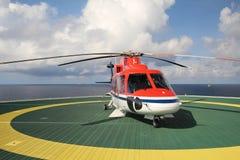 Работающ оффшорный, вертолет приземлился на снаряжение, море, изменяя стоковое фото rf