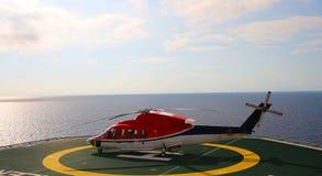 Работающ оффшорный, вертолет приземлился на снаряжение, море, изменяя стоковое изображение