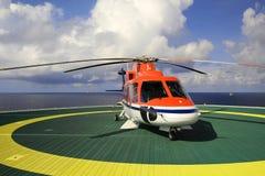 Работающ оффшорный, вертолет приземлился на снаряжение, море, изменяя стоковые фото