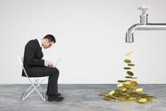 Работая бизнесмен с компьтер-книжкой и faucet от которой деньги стоковое изображение rf