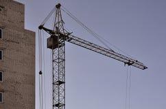 Работая высокорослые краны внутри места для с высоких зданий под конструкцией против ясного голубого неба Деятельность крана и зд Стоковые Фото