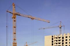 Работая высокорослые краны внутри места для с высоких зданий под конструкцией против ясного голубого неба Деятельность крана и зд Стоковые Изображения