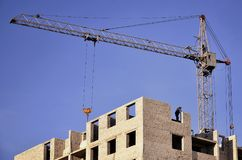 Работая высокорослые краны внутри места для с высоких зданий под конструкцией против ясного голубого неба Деятельность крана и зд Стоковые Изображения RF