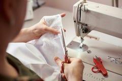 Работая женские руки используя ножницы для резать ткань в шить процессе r o стоковые изображения