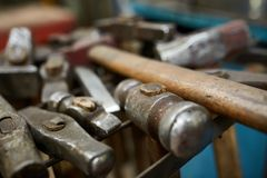 Работая инструменты металла в мастерской ` s кузнеца, конце-вверх, селективном фокусе, никто Стоковые Изображения RF