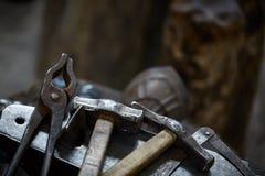 Работая инструменты металла в мастерской ` s кузнеца, конце-вверх, селективном фокусе, никто Стоковая Фотография