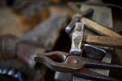 Работая инструменты металла в мастерской ` s кузнеца, конце-вверх, селективном фокусе, никто Стоковое фото RF