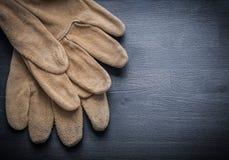 2 работая кожаных перчатки на темной деревянной доске Стоковое Фото