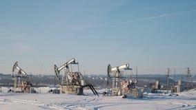 Работая масляные насосы в зиме field на предпосылке города сток-видео