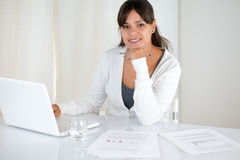 Работая молодая женщина смотря вас на офисе стоковые изображения rf