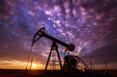 Работая нефтяная скважина нефти и газ и небо захода солнца Стоковое Фото