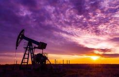 Работая нефтяная скважина нефти и газ и небо захода солнца Стоковые Фотографии RF