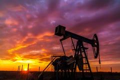 Работая нефтяная скважина нефти и газ и небо захода солнца Стоковая Фотография
