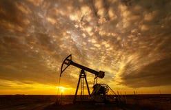 Работая нефтяная скважина нефти и газ и небо захода солнца Стоковые Изображения