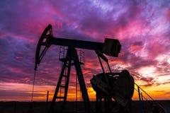 Работая нефтяная скважина нефти и газ и небо захода солнца Стоковое Изображение RF