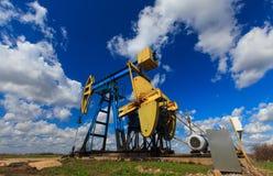 Работая нефтяная скважина нефти и газ профилированная на солнечном небе Стоковое Фото