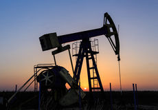 Работая нефтяная скважина нефти и газ хорошо профилированная на небе захода солнца Стоковая Фотография