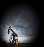 Работая нефтяная скважина профилированная на драматическом пасмурном небе Стоковое Изображение RF