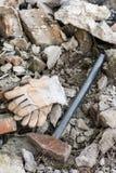 Работая перчатки с большим молотком над руинами Стоковое Фото