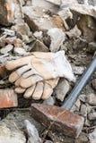 Работая перчатки с большим молотком над руинами Стоковые Фото