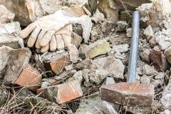 Работая перчатки с большим молотком над руинами Стоковые Изображения