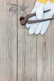 Работая перчатки с ногтями и пинцеты на серых деревянных досках Стоковое фото RF