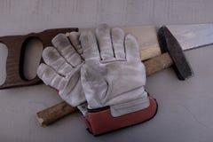 Работая перчатки с увидели и молоток Стоковое Изображение