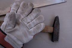Работая перчатки с увидели и молоток Стоковое Фото