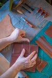 Работая процесс кожаного бумажника в кожаной мастерской Зашейте кожаное стоковое фото rf