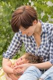 Работая родители Предпосылка счастья женщины Работница Дама с игрой ребенка на открытом воздухе стоковые изображения