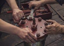 2 работая руки завинчивают большую гайку с ключем Стоковое Фото
