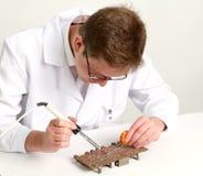 Работая электроника ремонтируя доску используя паяя ручку стоковые изображения