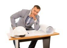 Работа архитектора сидя на плане на таблице Стоковые Фото
